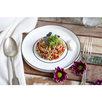 Quinoa Paradeiser Mix garniert auf gedecktem Tisch